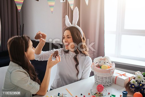 istock Cheerful mother and daughter prepare for Easter. They hold chocolate eggs and smile. Decoration on table. Model wear white rabbit ears. 1132323508