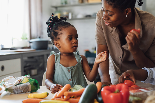 Cheerful African American mother and daughter preparing vegetables for lunch at the kichen table