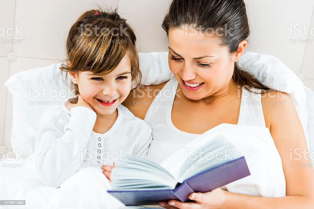 Cheerful mother and daughter reading a book in bed. royalty-free stock photo
