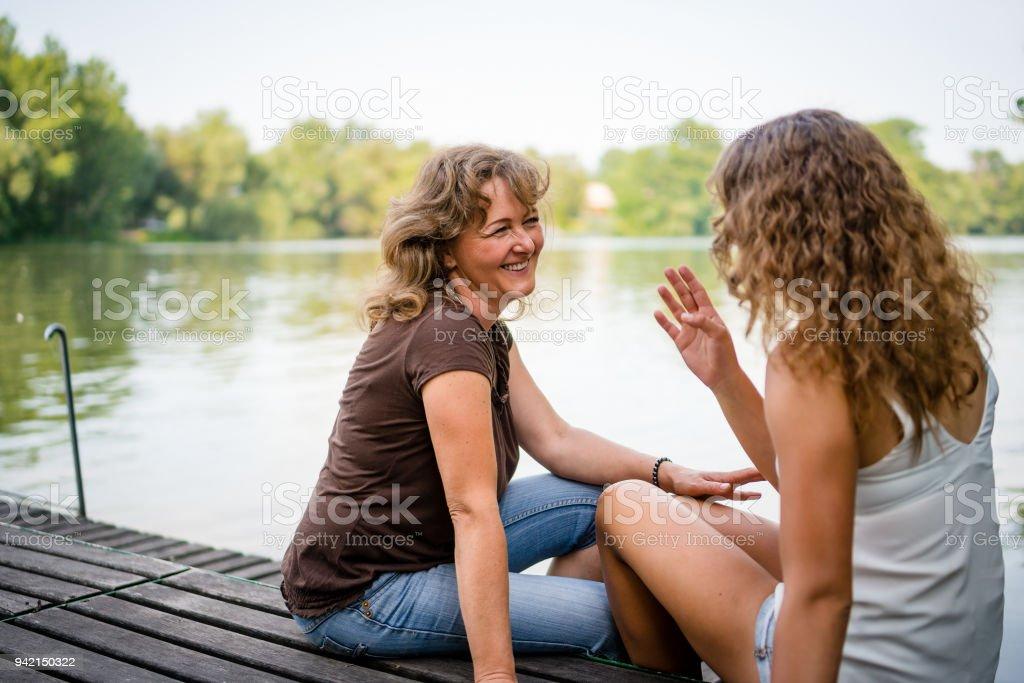 Fröhliche Mutter und Tochter sitzt auf der Kante von einem Holzsteg – Foto