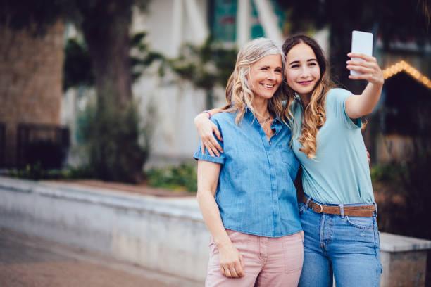fröhliche mutter und tochter unter selfies zusammen in der stadt - altes damenhaar stock-fotos und bilder