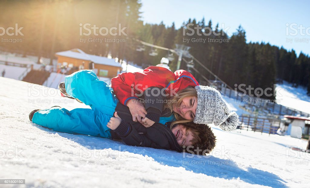 Cheerful mother and son having fun while playing on snow. photo libre de droits