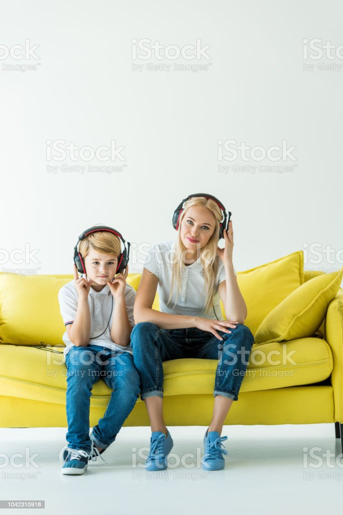 cheerful mother and son listening music with headphones on yellow sofa on white stock photo