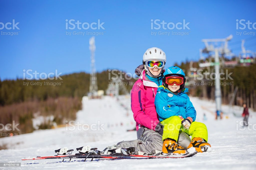 Cheerful mother and son resting on ski slope stock photo