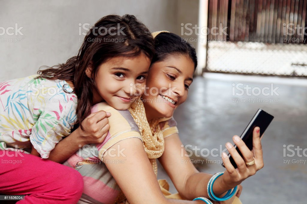 Cheerful  mother & daughter using mobile phone at home stock photo