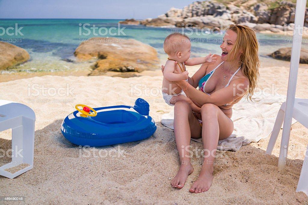 Fröhlich Mutter, die mit ihren kleinen Sohn auf den Strand. – Foto