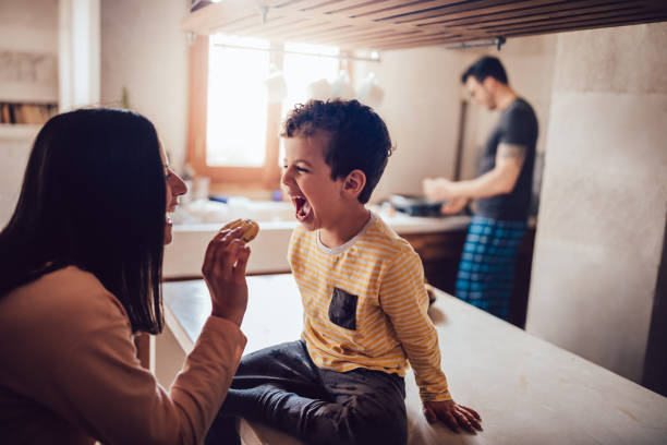 Cheerful mother giving little son cookie in the morning Boy sitting on kitchen counter in the morning with mother giving him cookie before breakfast wundervisuals stock pictures, royalty-free photos & images