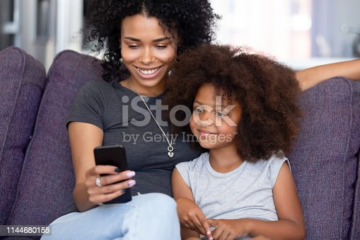 Happy afro mother or elder sister with little kid sitting on sofa in living room at home spend time using phone app having fun, watching cartoons make videocall, modern tech weekend activities concept