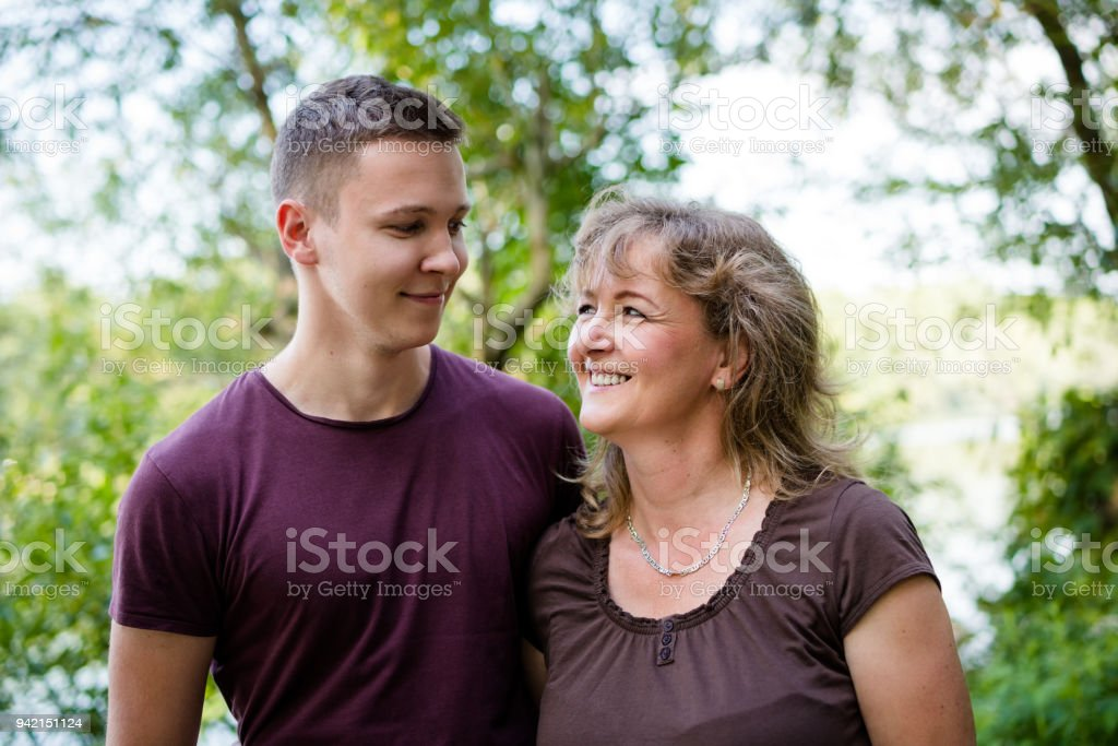 Cheerful mother with adult son outdoors. Family concept. stock photo