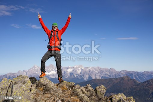 happy smiling successful mature adult man hiker mountaineer standing mountain peak both arms raised up on sunny day in autumn with beautiful mountains panorama blurred in background with place for text
