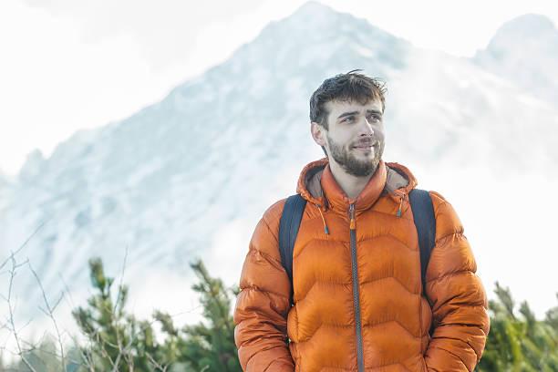 fröhlich bergsteiger stehend im beeindruckenden winter hohen gipfeln landschaft hintergrund - gute winterjacken stock-fotos und bilder