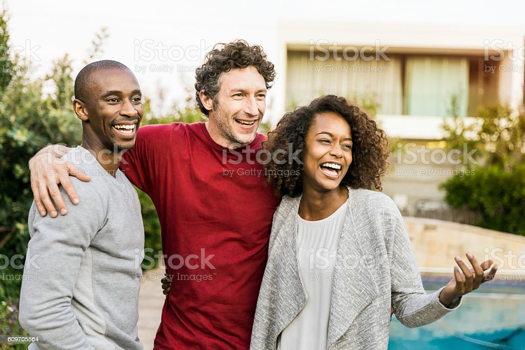 Cheerful multi-ethnic friends standing in yard – zdjęcie