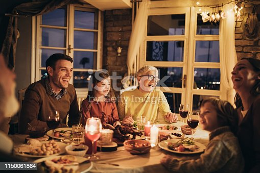 Happy extended family having fun while talking during dinner time at dining table.