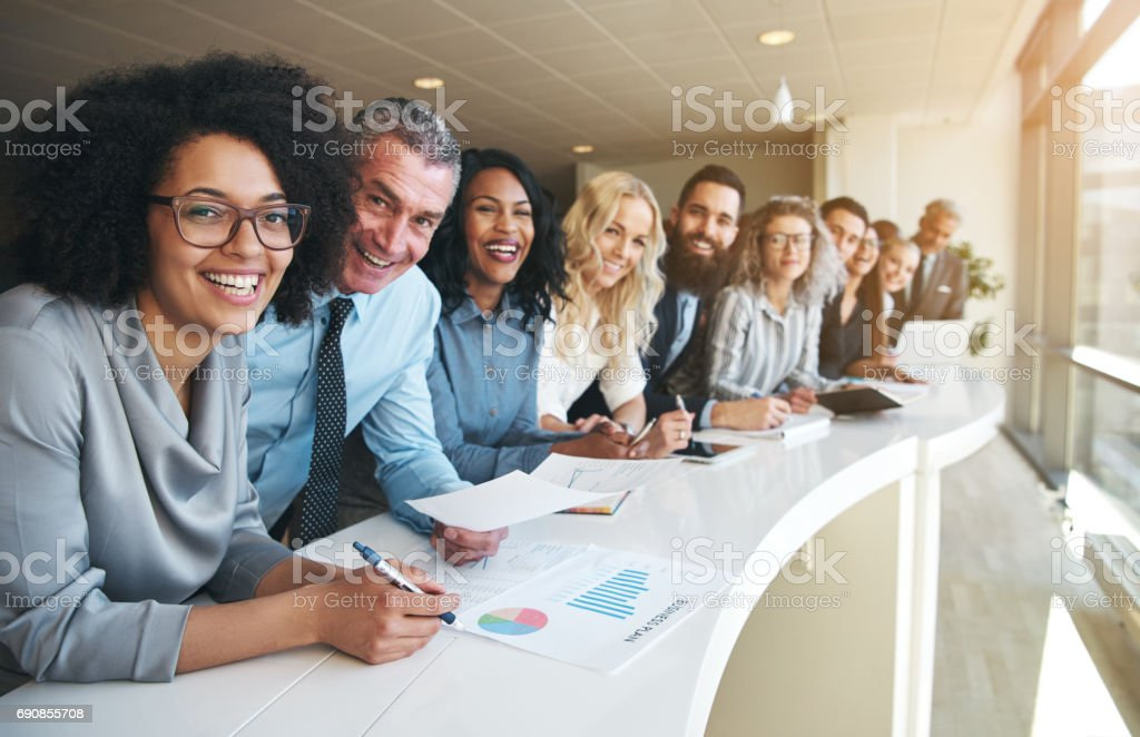 Cheerful multiracial colleagues looking at camera in office Smiling black and white coworkers looking at camera in the office. Adult Stock Photo