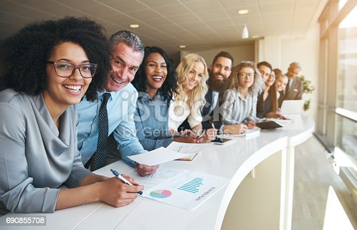 istock Cheerful multiracial colleagues looking at camera in office 690855708