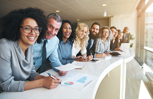 690855708 istock photo Cheerful multiracial colleagues looking at camera in office 690855708