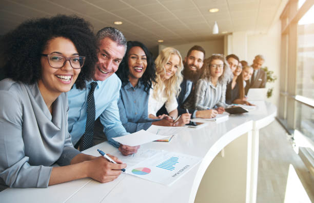 cheerful multiracial colleagues looking at camera in office - office job stock photos and pictures