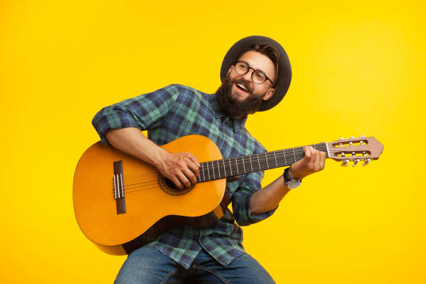 Cheerful musician with guitar Smiling bearded musician man having fun and playing acoustic guitar. guitarist stock pictures, royalty-free photos & images