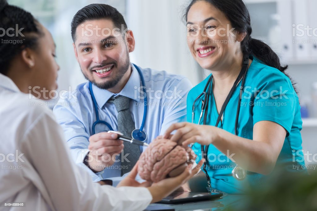 Cheerful neurologist and nurse explain patients diagnosis stock photo