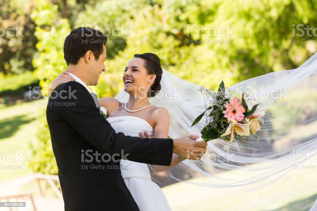 Cheerful newlywed couple dancing in park stock photo