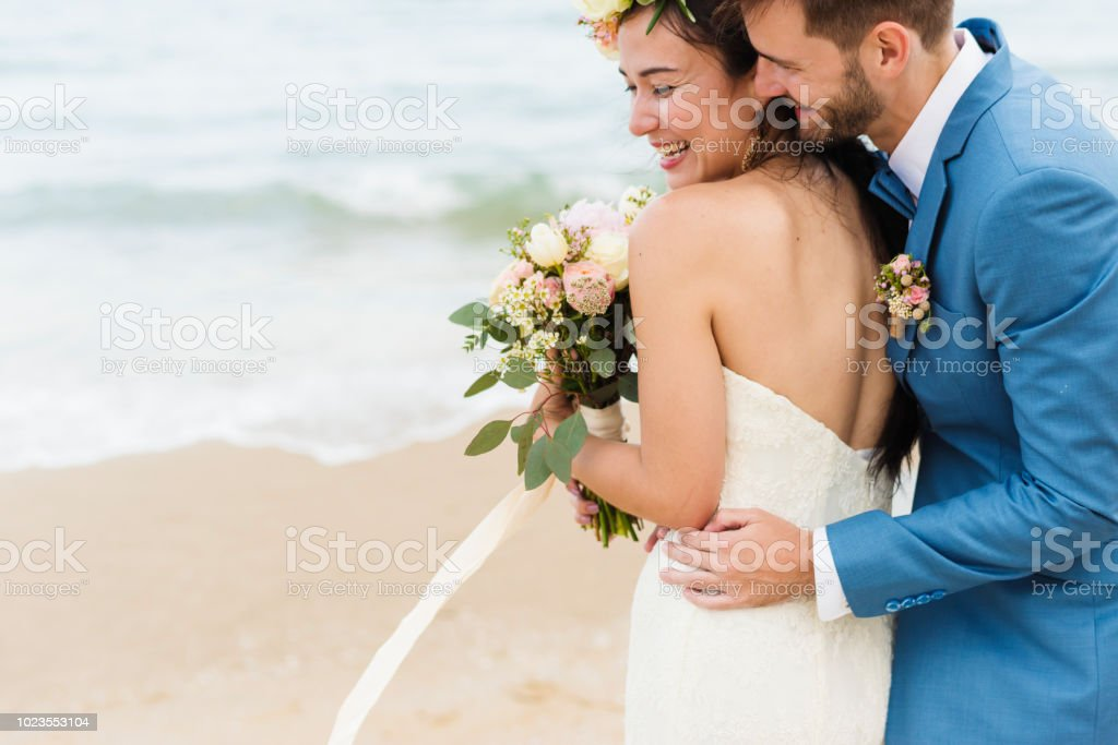 Cheerful newlyweds at beach wedding ceremnoy stock photo