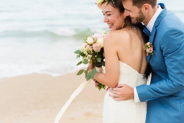 recién casados alegres en playa boda ceremnoy - boda fotografías e imágenes de stock