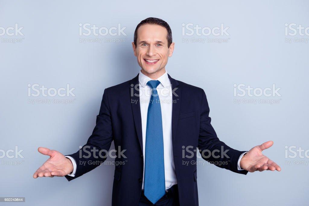 Neşeli, güzel kravat misafirperver jest gibi elleri açık olması ile formal giyim erkek, sen de bir araya geldi, gri arka plan üzerinde duran hoş geldiniz stok fotoğrafı