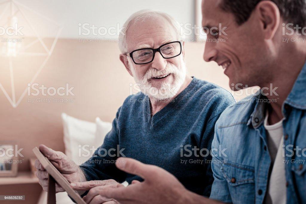 Fröhlicher netter Mann im Gespräch mit seinem Großvater – Foto