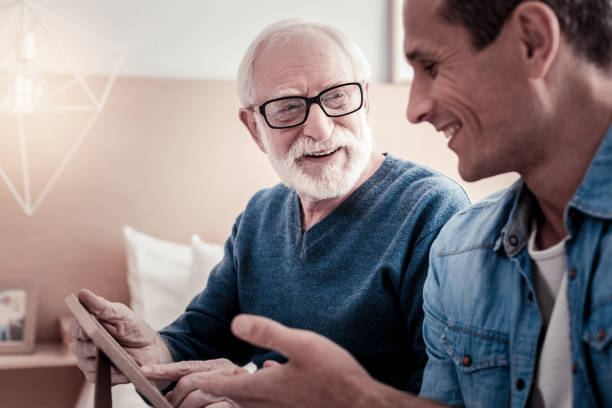 Cheerful nice man talking to his grandfather stock photo