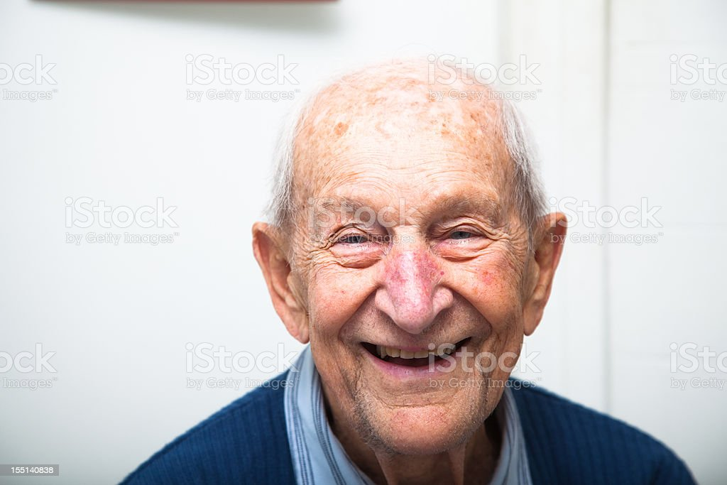 Cheerful ninety year old senior man in his house Happy senior man ninety years old in his house against a slightly defocussed white background. 80-89 Years Stock Photo