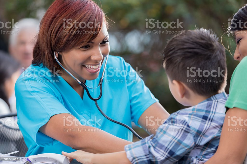 Cheerful nurse checks boys heartbeat at free outdoor clinic stock photo