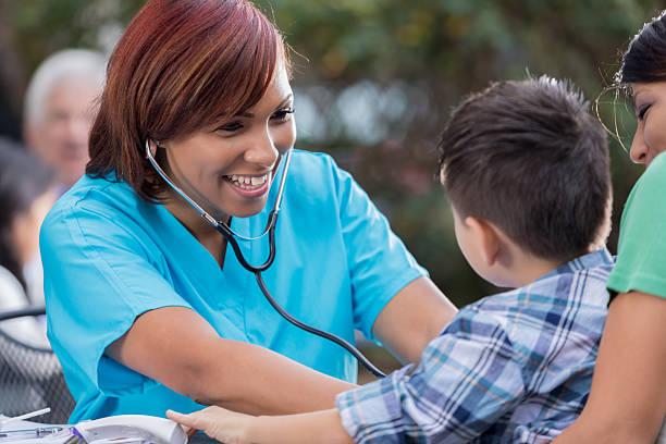 Cheerful nurse checks boys heartbeat at free outdoor clinic stock photo