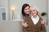 Strong bond. Joyful nurse embracing elder woman who smiling to camera