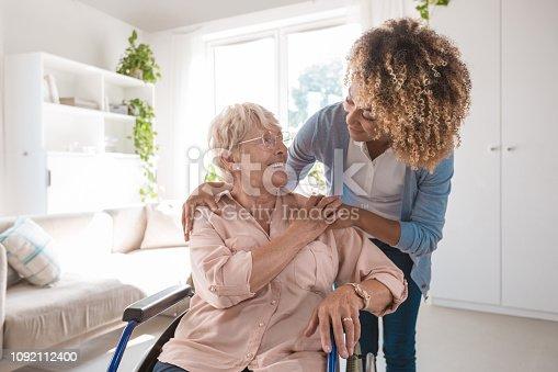istock Cheerful nurse taking care of eldery lady 1092112400