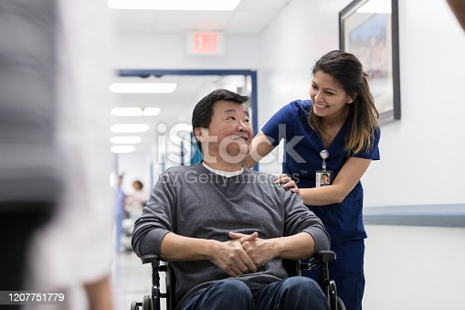 Smiling senior man talks with a friendly nurse in a hospital hallway. The nurse is pushing the man in a wheelchair.
