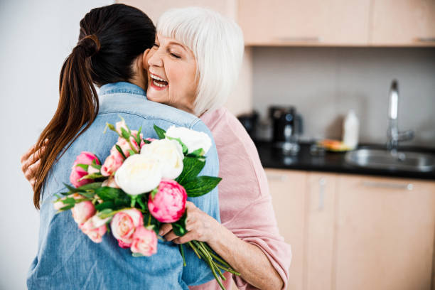 Cheerful old lady holding flowers and hugging granddaughter stock photo
