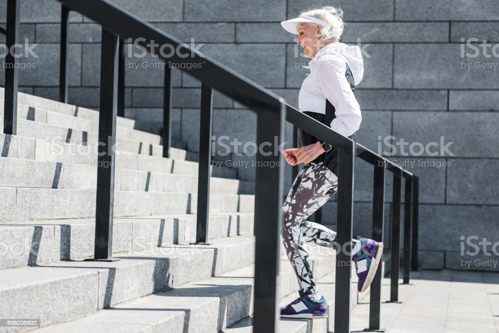 Cheerful old lady training to run up concrete stairs stock photo