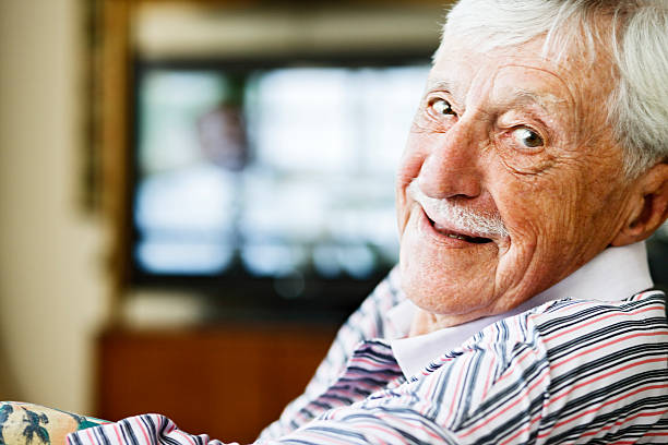 Cheerful old man looks over shoulder from watching television stock photo