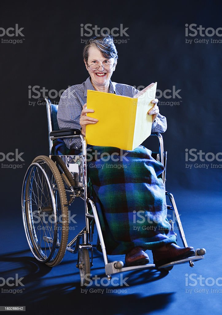 Cheerful old woman in wheelchair reads book royalty-free stock photo