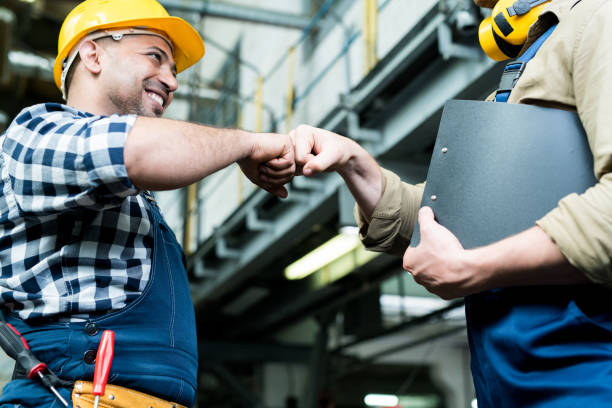 Cheerful optimistic factory colleagues in workwear making fist bumps while celebrating successful job at industrial plant stock photo