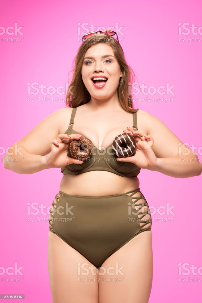cheerful overweight girl with donuts stock photo