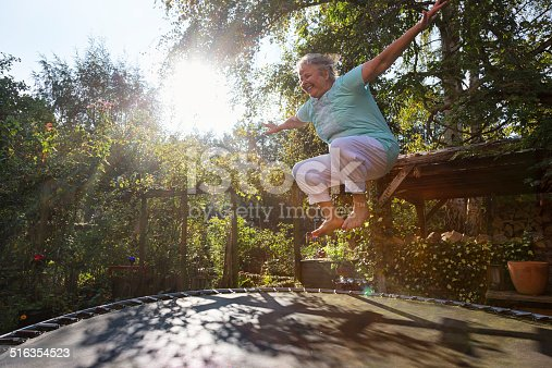 senior woman, 60 yeas old, with overweight, but enjoying to jump on trampoline in garden, file contains lens flares