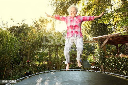 senior woman, 60 yeas old, with overweight, but enjoying to jump on trampoline in garden
