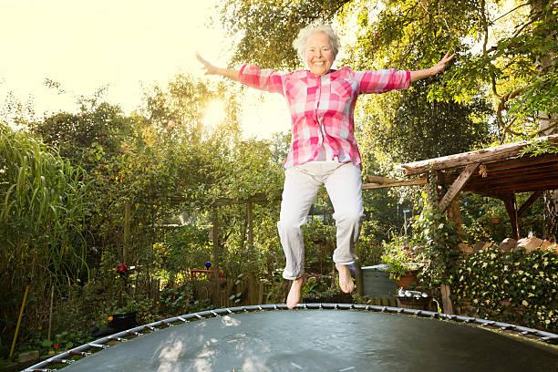 fröhlich dick senior frau springen auf trampolin - gartentrampolin stock-fotos und bilder