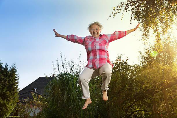fröhlich dick senior frau springen - gartentrampolin stock-fotos und bilder