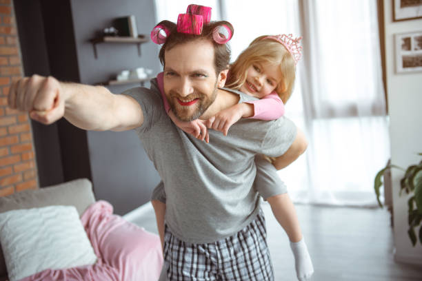 Cheerful parent playing a super hero with girl stock photo