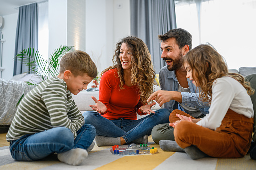 Young parents playing ludo game with their kids and having fun at home.