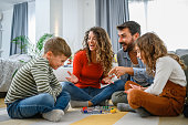 istock Cheerful parents playing board game with their children. 1286003631