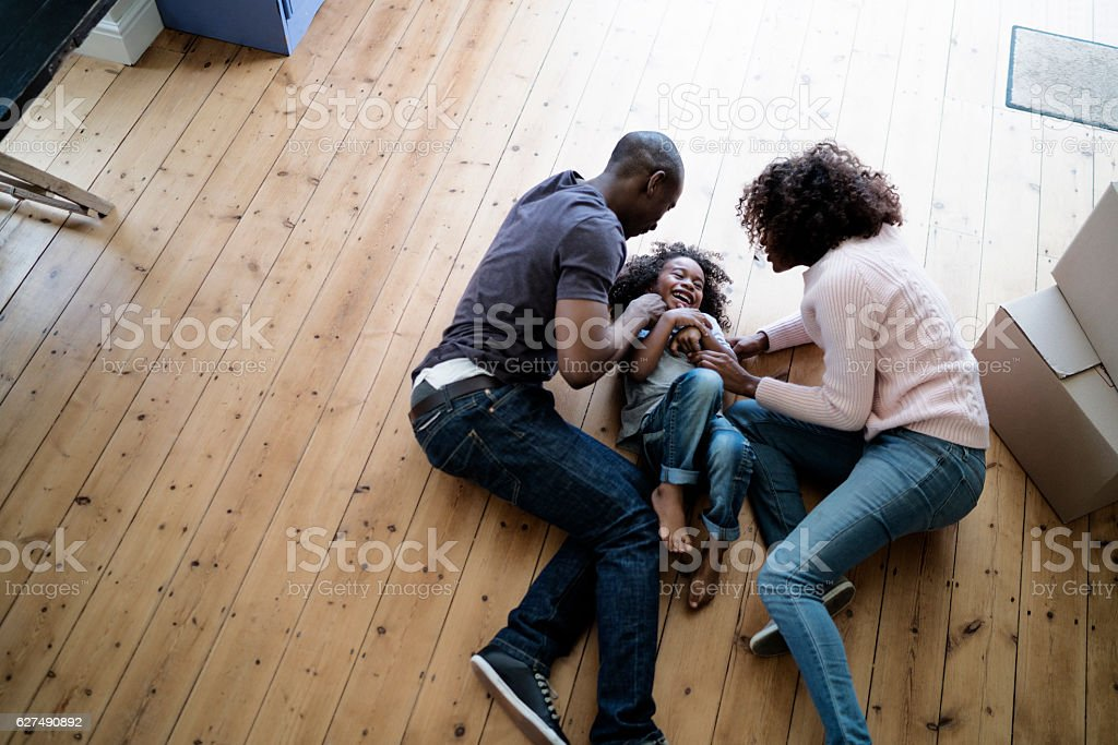 Cheerful parents playing with son on at new home stock photo