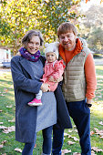 Cheerful parents with cute little baby posing for photo in park together. Blonde mother holding daughter. Family with child standing on grass with fallen maple leaves. Parenthood and weekend concept